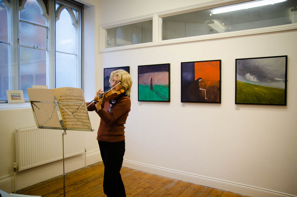 Image shows four painting on a wall, block coloured. In the foreground, a woman plays a violin