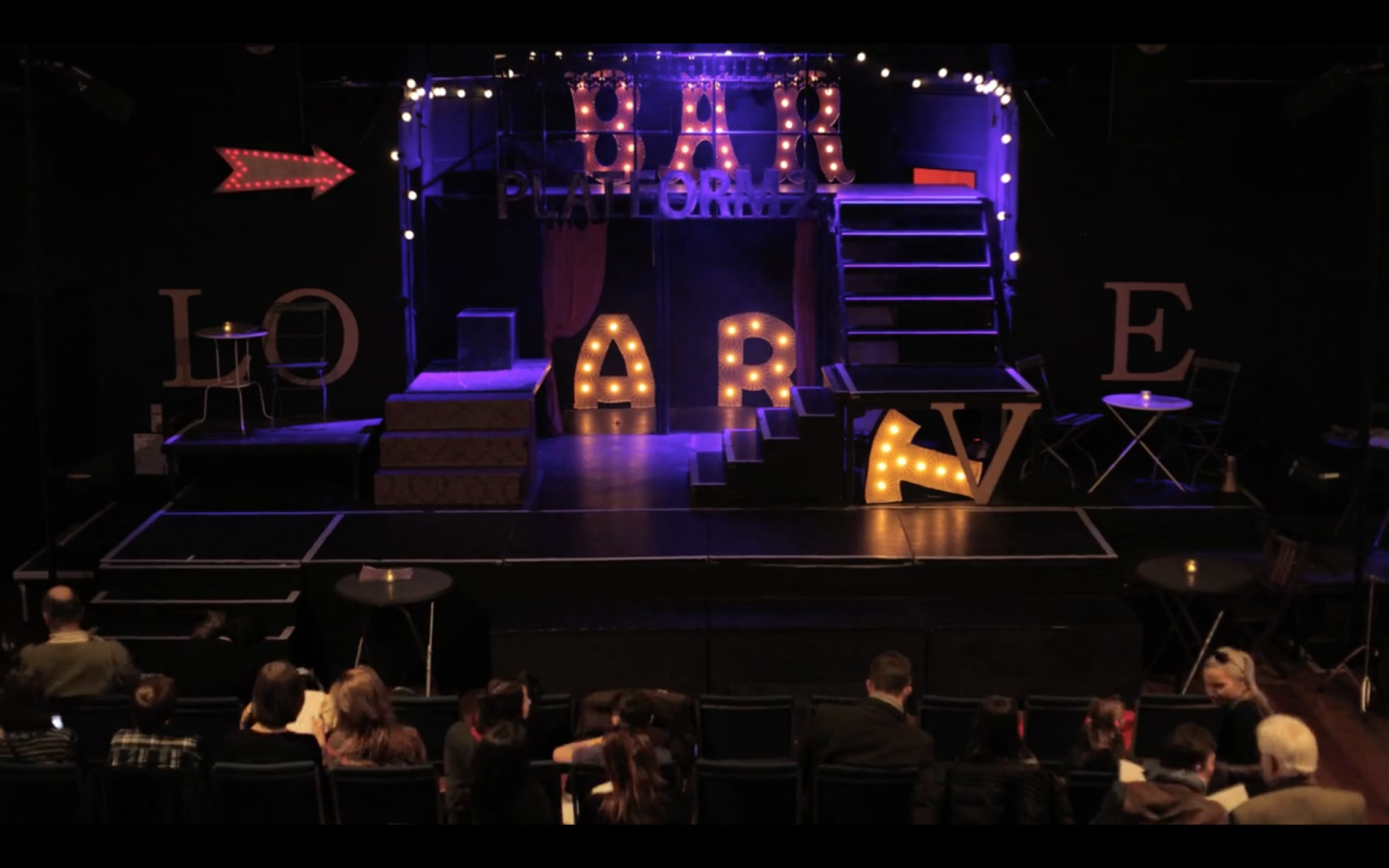 Image shows a stage set up with with stairs and lights. The lights read BAR in the centre, LOVE spread across either side of the stage. An arrow points to a raisaed platform, and other lights run around the edge of the platform. The audience is gathering