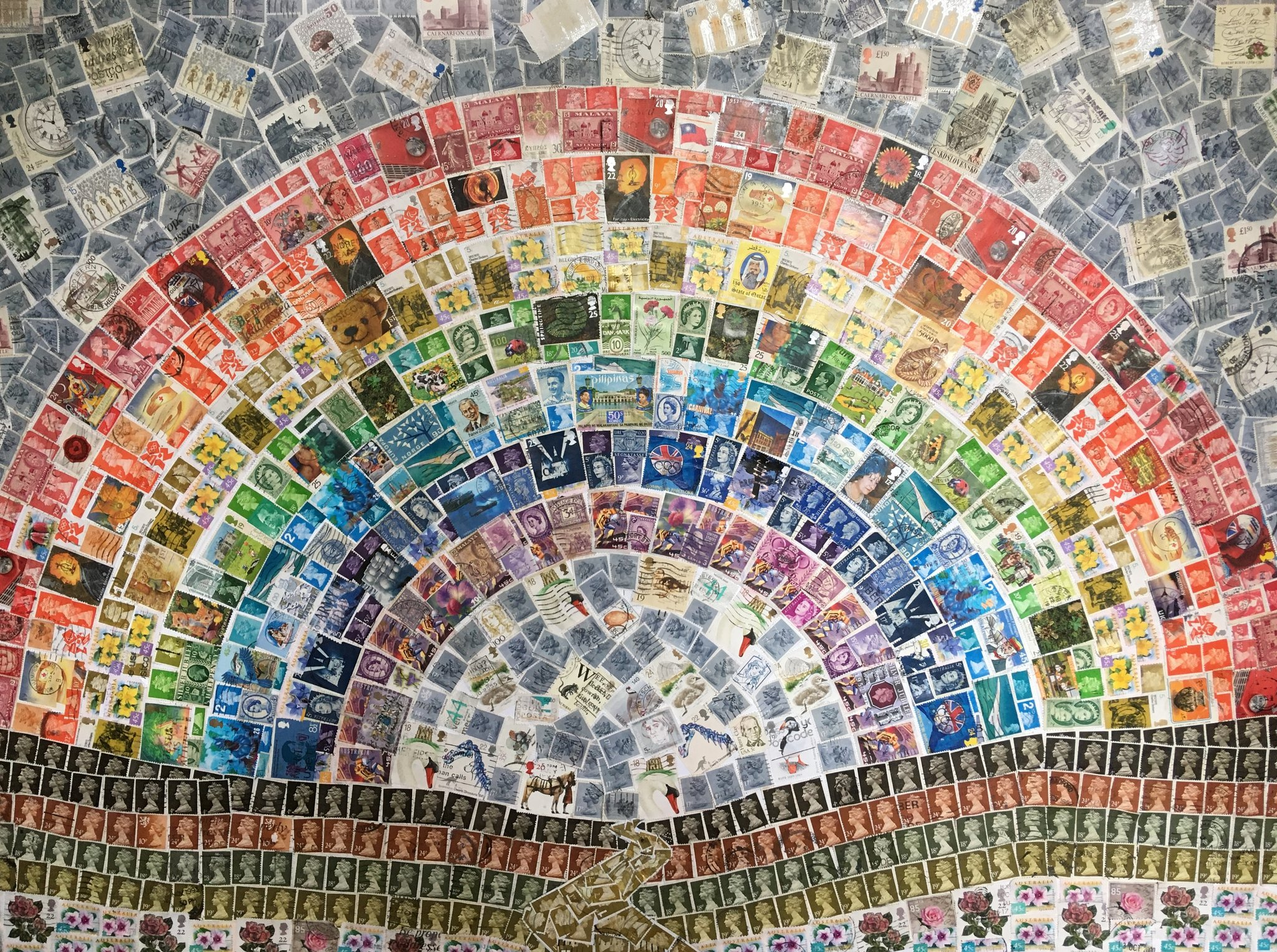 Image shows a rainbow made of stamps. Title of piece is Stamp Arc, by Helen Wood
