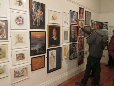 Image shows a wall full of paintings and drawings mainly of people