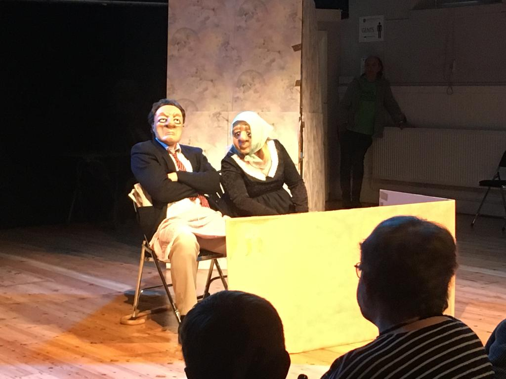 Image shows two actors wearing masks performing in a play
