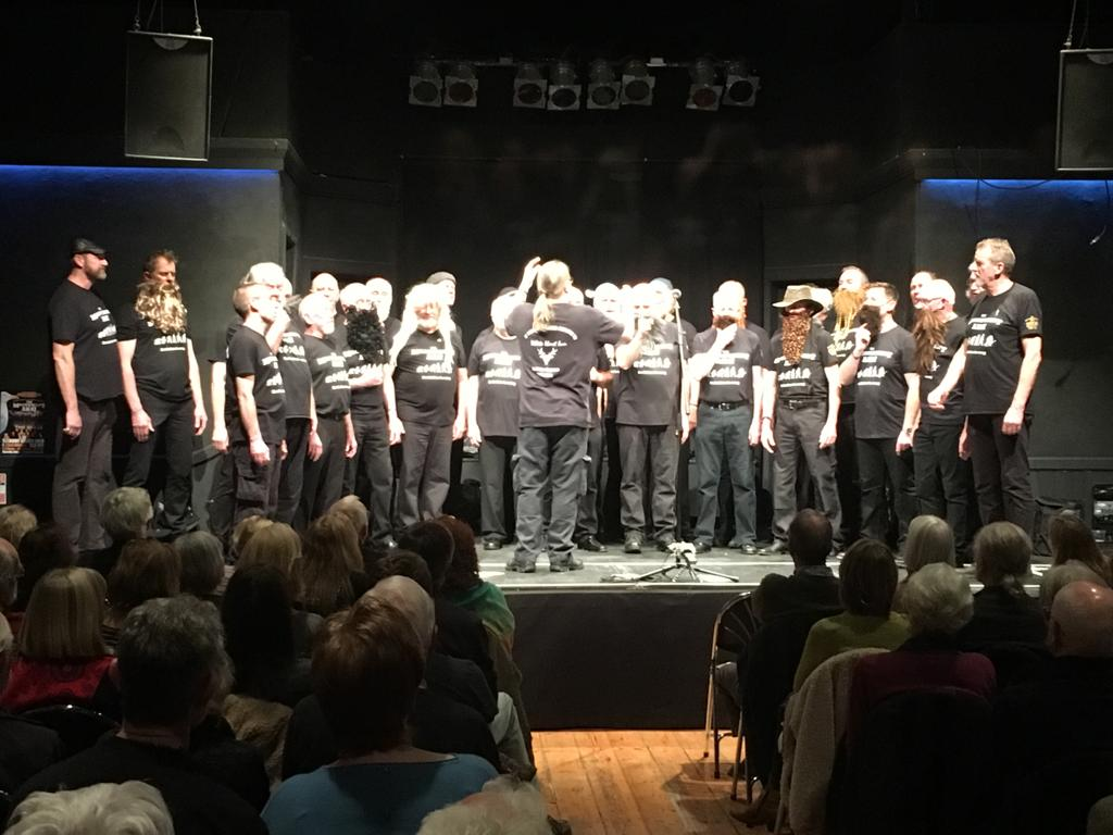 Image shows a choir with lots of beard. Some of the beards may be fake