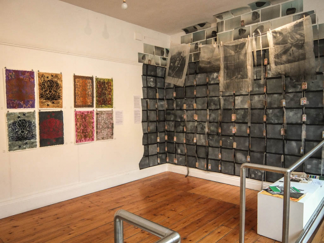 Image shows an exhibition of prints and photos on fabric
